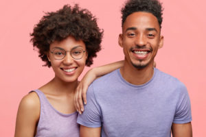 couple smiling against pink background